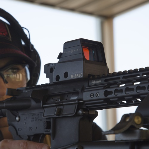 Woman shooting an AR-15 with a Sightmark red dot sight mounted to it